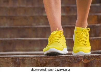 Close-up of man's running shoes while walking towards the camera.