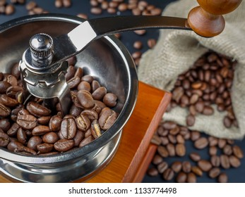 Closeup of manual coffee grinder filled with coffee beans