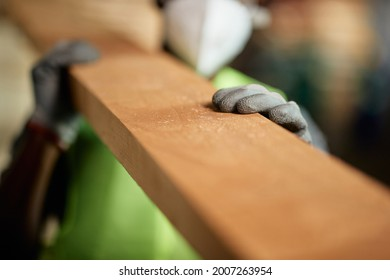 Close-up of manual worker carrying timber while working at wooden warehouse.