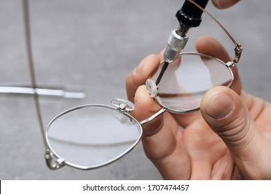 Closeup of manufacturing medical glasses with ophthalmology tool in clinic office. Young optician is repairing broken eyeglasses nosepad in workshop. Vision concept