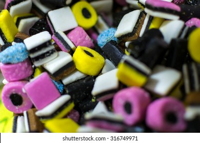 Closeup of many assorted liquorice sweets in different colors and shapes on display at a local farmer's market