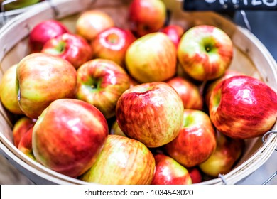 Closeup of many cortland pink lady honeycrisp red yellow apples in wooden basket at farmer's market shop store showing detail and texture
