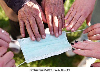 Nahaufnahme von vielen verschiedenen Händen junger Menschen mit Händen einer älteren Frau in der Mitte, die Pflege der älteren Menschen inmitten der Pandemie des Coronavirus symbolisiert.