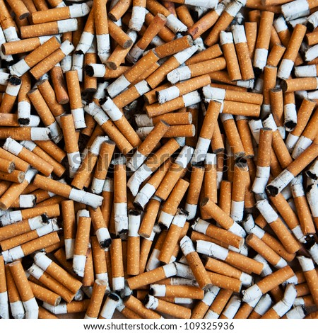 closeup of many dirty cigarettes butts background