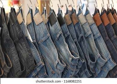 Closeup many jeans hanging on a rack. Row of pants denim jeans hanging in closet. concept of buy , sell , shopping and jeans fashion.