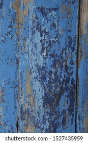 closeup of many layers and shades of blue paint pealing and weathered on wood door