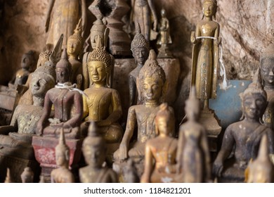 Close-up of many old and faded, golden and wooden Buddha statues inside the Tham Ting Cave at the famous Pak Ou Caves near Luang Prabang in Laos.