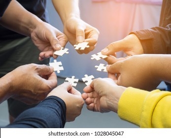 Close-up of many people hands holding a jigsaw puzzle piece in circle together with sunlight effect. Unity and Teamwork Concept.