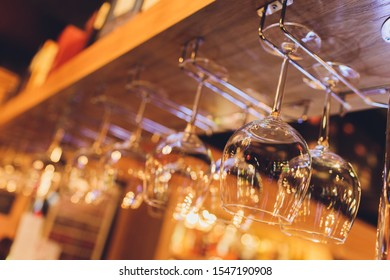 Closeup many upside down empty clear transparent crystal upturned wine glasses hanging in straight rows on brown wooden shelf, rack, showcase, stainless steel railing in bar, cabinet.