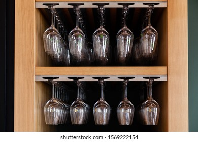 Closeup many upside down empty clear transparent crystal upturned wine glasses hanging in straight row on brown wooden shelf, rack, showcase, stainless steel railing in bar, cabinet
