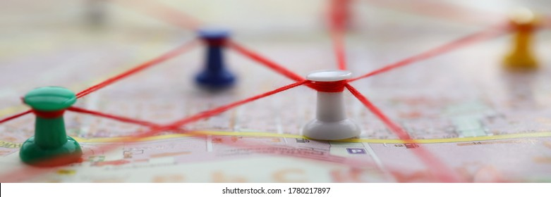Close-up of map marked with red thread paths of movement. Plan of street with buttons forming route. Pedestrian building route around city. Navigation concept