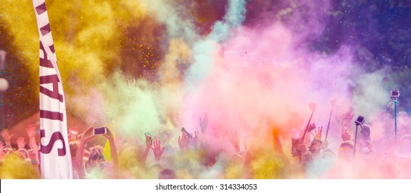 Close-up of marathon runners with colored powder in the air