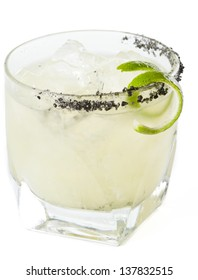closeup of a margarita garnished with smoked black lava salt isolated on a white background