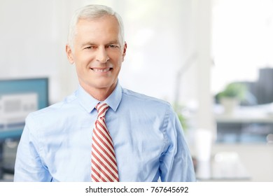 Close-up of a marketing director businessman standing in the office while looking at camera and smiling.