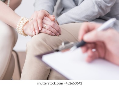Close-up of married couple's hands in an affectionate pose and a blurred flipboard with somebody writing on it