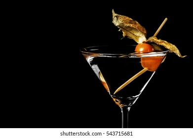 Close-up of martini with physalis on black background