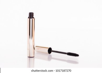 Closeup Mascara Bottle and Brush. Black Mascara wand and Tube Isolated on White. Gold Bottle. Mascara on Light Background, New Form Brush. Mascara New Formula on white Background with Brush