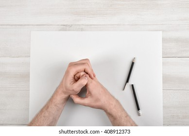 Closeup masculine folded hands on wooden panel with white paper and broken black pencil in top view.