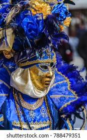 Close-up of masked woman wearing blue and gold costume during the Carnival in Venica, Italy