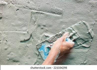 Closeup mason hand spreading fresh concrete mix with trowel