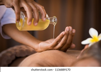 Closeup of masseur hands pouring aroma oil on woman back. Masseuse prepare to do oriental spa procedure for relaxing treatment. Therapist doing aromatherapy oil massage on woman body.