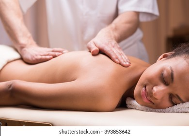 Close-up of masseur stroking woman's back during massage