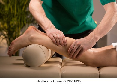 Close-up of masseur's hands kneading female calf