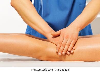 Close-up of masseur's hands kneading female leg