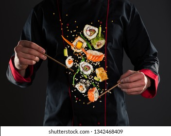 Closeup of master chef holding wooden chopsticks with flying sushi pieces. Concept of food preparation, ready for product placement.