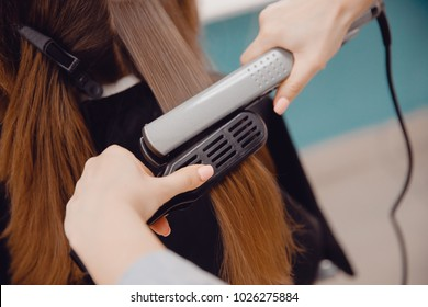 Close-up of master hairstylist ironing for straightening hair restores keratin.