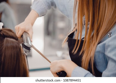 Close-up of master hairstylist ironing for straightening hair restores keratin and straightens hair.