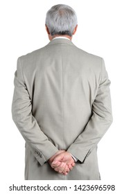 Closeup of a mature, businessman seen from behind with his hands clasped behind his back.