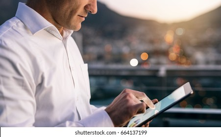 Closeup of a mature businessman working online with a digital tablet while standing outside on an office building balcony overlooking the city at dusk