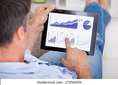 Close-up Of A Mature Man Analyzing Graph On Digital Tablet
