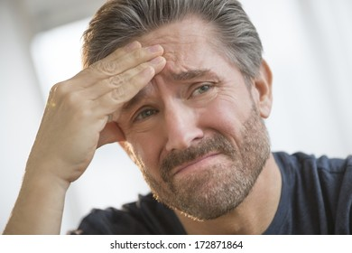 Closeup of mature man with headache rubbing forehead