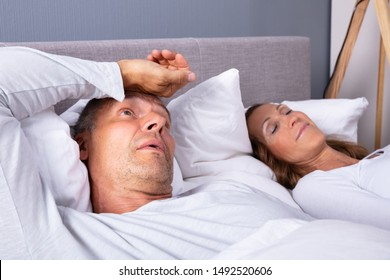 Close-up Of Mature Man With Insomnia Lying On Bed Next To His Wife At Home