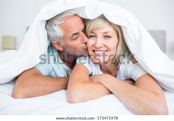 Nahaufnahme eines reifen Mannes, der die Frauen küsst, im Bett zu Hause Wangen