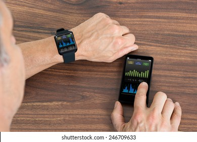Close-up Of Mature Man With Smartwatch And Cellphone Showing Heartbeat Rate Sitting At The Table