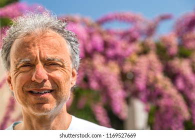 closeup of mature man smiling with broken tooth, grey hair and three days beard on bougainvillea flowers background