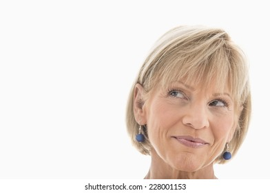 Close-up of mature woman looking away over white background