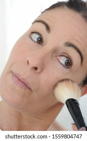 close-up of mature woman puts the fard on her cheeks