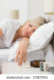 Closeup of a mature woman sleeping in bed with pills in foreground at home