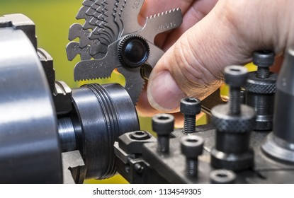 Close-up of measurement by thread pitch gauge. Detail of a machinist's hand with the set of threaded gauges. Threading by a steel tool bit on a lathe. Idea of machining, metalworking, engineering.