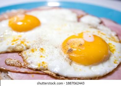 Closeup of a meat sandwich with fried egg. Yellow egg yolk. Dutch lunch Uitsmijter. - Shutterstock ID 1887062443