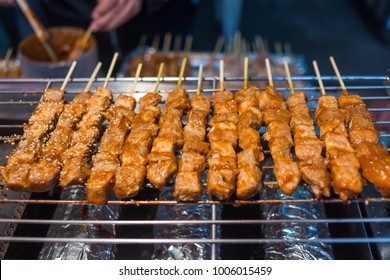 Closeup of meat skewers being grilled in a barbecue, street food in Taipei, Taiwan