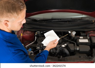 Close-up Of A Mechanic Checking Oil Level In Car Engine
