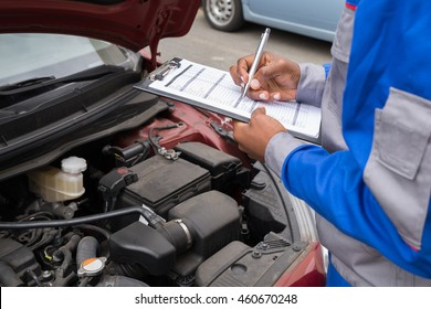 Close-up Of A Mechanic With Clipboard Checking Car Engine