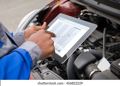 Close-up Of Mechanic With Digital Tablet Showing Graph While Examining Car