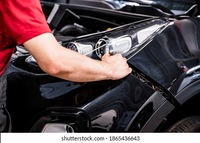 Close-up of mechanic hands dismantling the bumper of the car