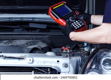 Closeup mechanic hands are holding special diagnostic equipment, scanner at vehicle with open hood. Repairman is repairing car and detecting problems at service station car repair shop.